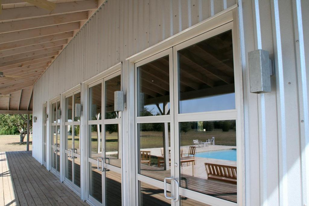 "<a href=""/node/175"">CUSTOM COMMERCIAL DOORS SPAN THE WIDTH OF THE BACK PORCH PAIRED WITH CUSTOM GALVANIZED TUBE STEEL SCONCES. ALL THESE FEATURES EMANATE THE CONTEMPORARY FEEL OF THE EXTERIOR BLENDING PERFECTLY WITH THE GALVALUME SIDING.</a>"